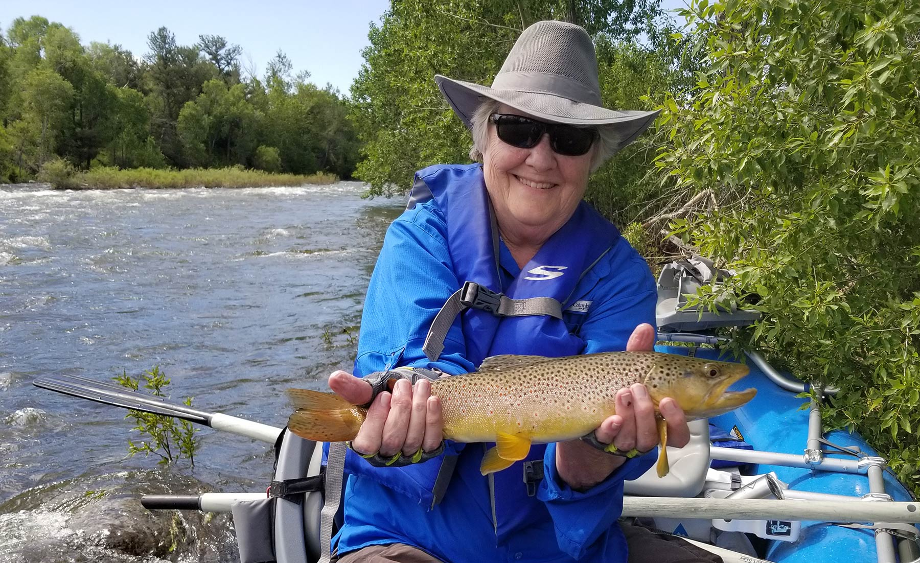 female angler with large boulder river brown trout